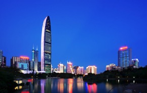 Night time view of Shezhen with water in the foreground and high rise building in the background - bright city lights