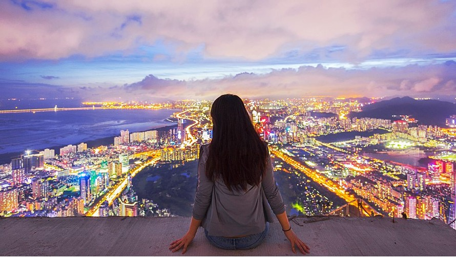 Image of a young woman sat high above a city looking out over the city at dusk, with bright city light