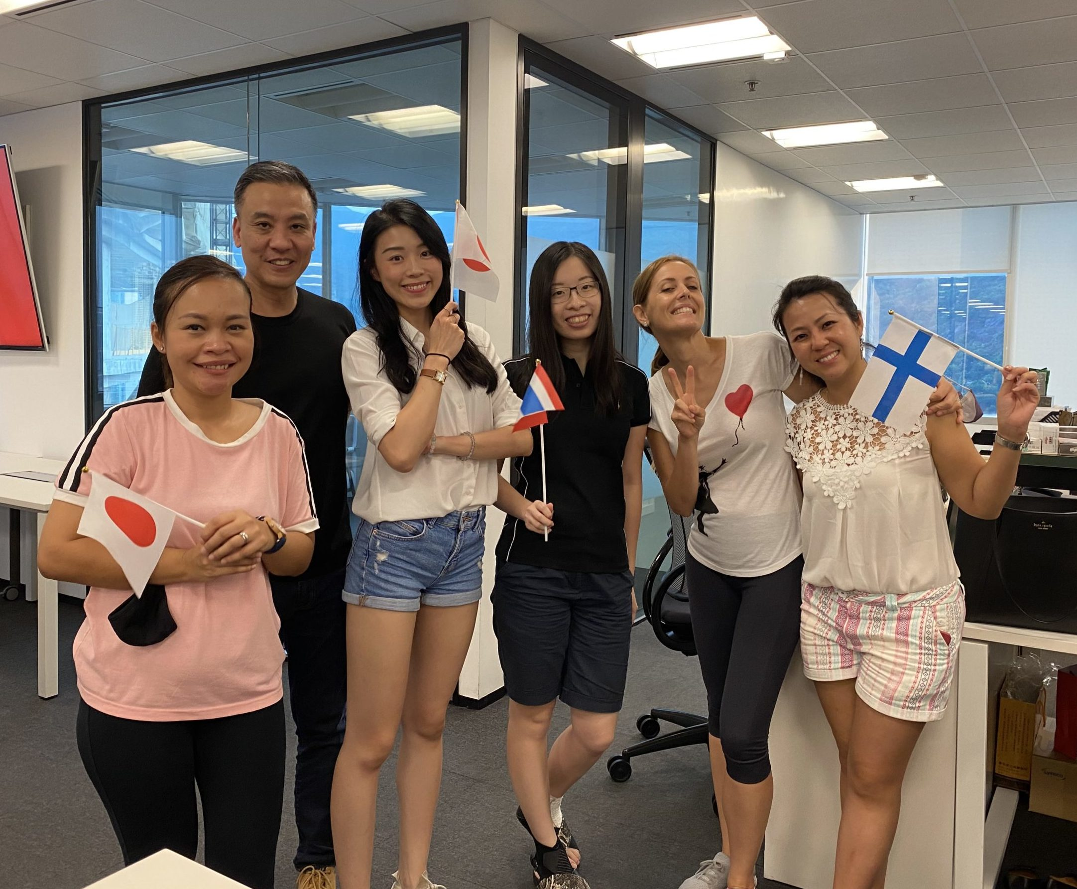 A group of five women and one man taking part in the gravitonian games pose for a photo in an office holding flags of different Olympic countries
